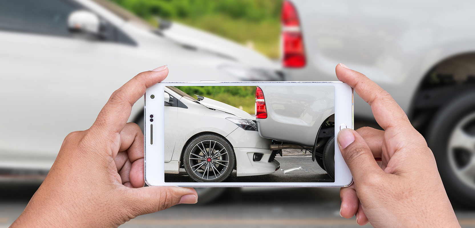 Image showing two crashed cars and person taking picture with cell phone camera.